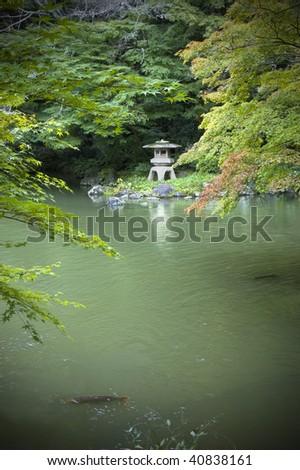 Japanede garden with Koi pond,carps and lantern. Vertical shot. - stock photo