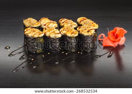 Japanese baked sushi and roll set on a wooden black table with ginger and sauce - stock photo