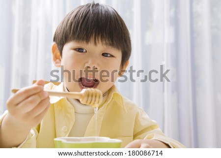 Japanese boy eating honey