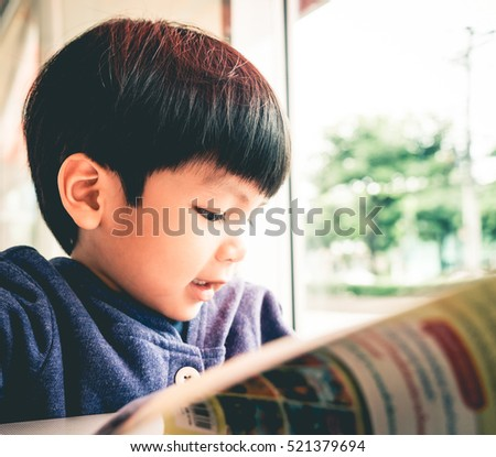 Japanese boy is reading a book in a Cafe windows.