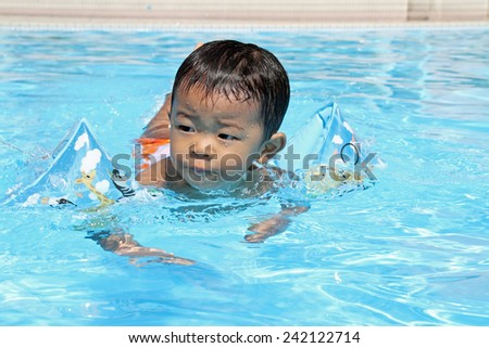 Japanese boy swiming in the pool (1 year old) - stock photo