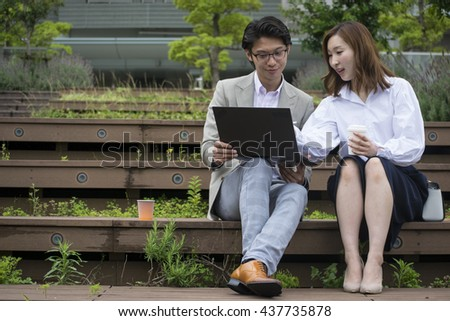 Japanese businessman and businesswoman talking whilst using a laptop computer and sitting outside on some steps in Tokyo