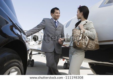 Japanese businessman and Korean businesswoman holding hands at airfield - stock photo