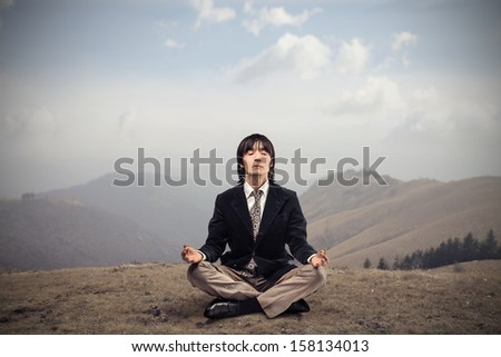 Japanese businessman meditating sitting ont he grass in the mountain