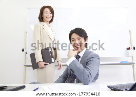 Japanese businesswoman and businessman smiling in a conference room
