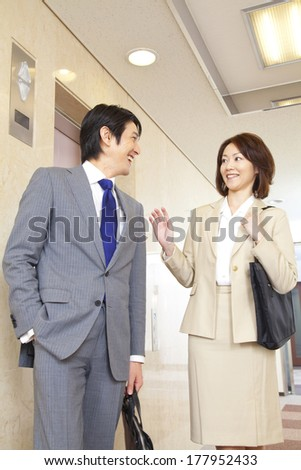 Japanese businesswoman and businessman walking down the hall