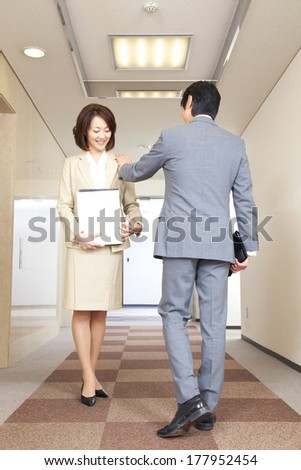 Japanese businesswoman and businessmen talking in the corridor