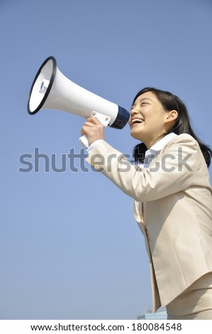 Japanese businesswoman crying out through a megaphone