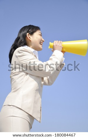 Japanese businesswoman crying out through megaphone