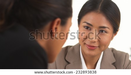 Japanese businesswoman talking with Mexican colleague - stock photo