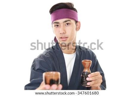 Japanese chef holding up a bottle of sake - stock photo
