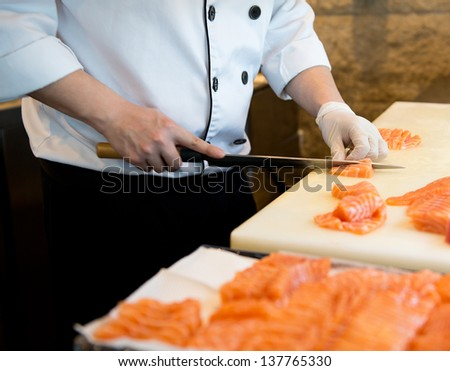 Japanese chef making sashimi in kitchen - stock photo