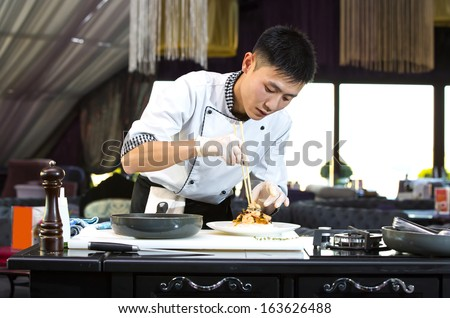 Japanese chef with a plate of sushi - stock photo