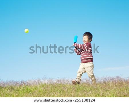 Japanese child swings the bat - stock photo