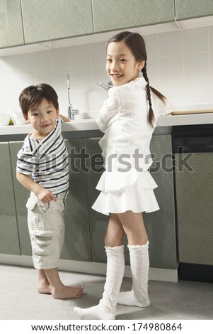 Japanese Children helping do the dishes - stock photo