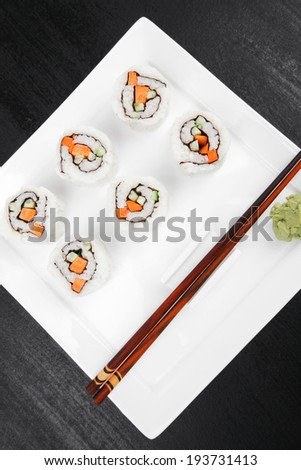 Japanese Cuisine - California Roll made of Raw Salmon, Cream Cheese and Deep Fried Vegetables inside. With wasabi . over black table