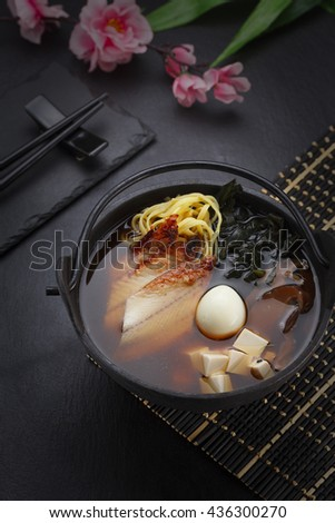 Japanese cuisine. Eel soup with homemade and ramen noodles on a black table