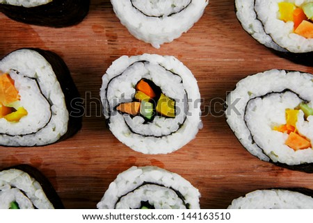 Japanese Cuisine - Maki Roll with Deep Fried Vegetables inside . on wooden plate . isolated over white background - stock photo