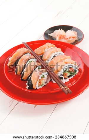 Sushi rolls with ginger and sake cup on red plate over white wooden
