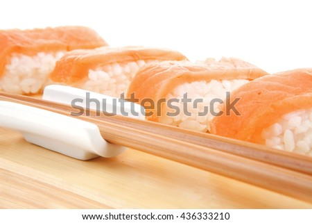 Japanese Cuisine - Set of Nigiri sushi topped with raw Salmon . on wooden board . isolated over white background - stock photo