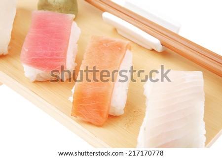 Japanese Cuisine - Set of Tuna (maguro) Salmon (sake) and Eel (unagi) Nigiri Sushi  with Wasabi on wooden plate isolated over white background - stock photo