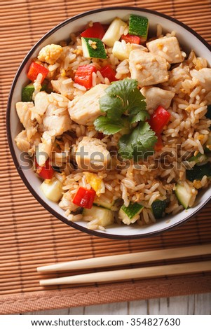 Japanese cuisine: Tyahan with chicken and vegetables close up in a bowl on the table. vertical top view