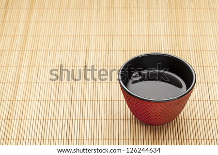 Japanese cup of tea on a bamboo mat - a traditional cast iron red hobnail design with black enamel inside - stock photo