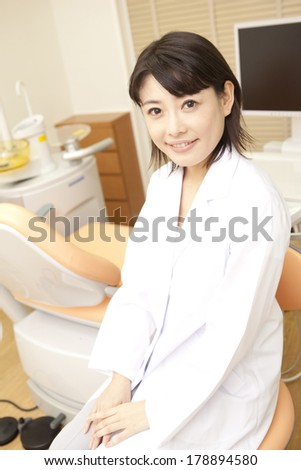 Japanese dentist sitting in front of the treatment table