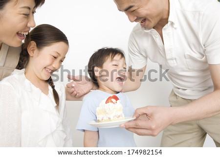 Japanese family eating cake - stock photo