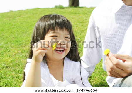 Japanese Father and girl picking dandelions - stock photo