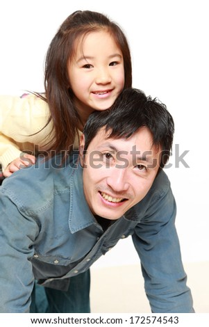Japanese father and his daughter play horse-ride