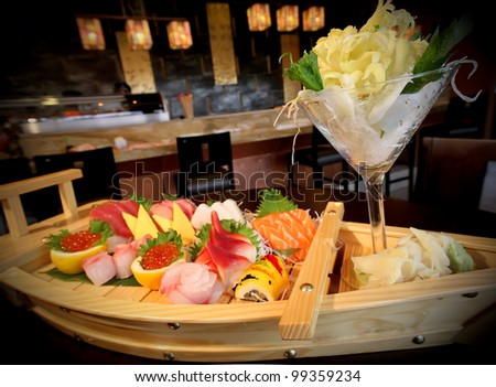 Japanese fine dining with Sushi and slices of salmon, tuna and eel Sashimi beautifully decorated on a wooden boat.