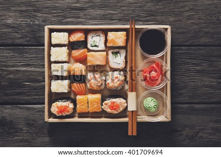 Japanese food restaurant, catering, maki gunkan roll plate or platter set. Sushi with chopsticks, ginger, soy sauce, wasabi at rustic wood background in take away, sushi set delivery box. Top view.  - stock photo