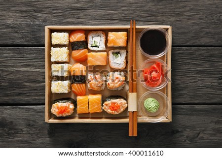 Japanese food restaurant, catering, sushi maki gunkan roll plate or platter set. Chopsticks, ginger, soy sauce, wasabi. Sushi at rustic wood background in take away, sushi set delivery box. Top view.  - stock photo