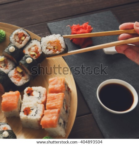 Japanese food restaurant, maki plate, platter set. Hand takes roll. Set with chopsticks, ginger, soy sauce at rustic wood background and black stone. POV at black. Instagram style.  - stock photo