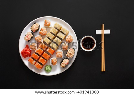 Japanese food restaurant, sushi maki gunkan roll plate or platter set. Chopsticks, ginger and wasabi. Sushi at white round plate, black background. Top view with soy sauce - stock photo