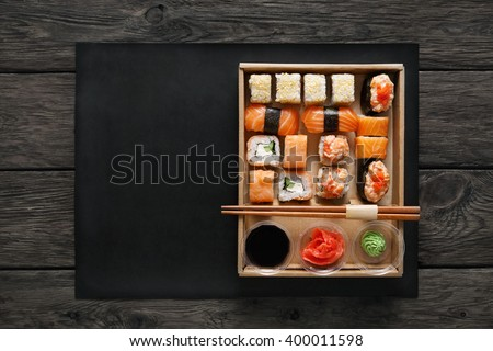 Japanese food restaurant, sushi maki gunkan roll plate or platter set. Free, copy space, chopsticks, ginger, soy sauce, wasabi. Sushi at rustic wood background in take away, delivery box. Top view.  - stock photo