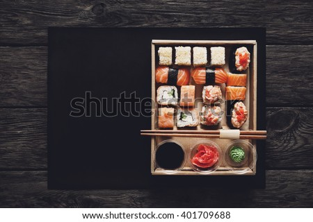 Japanese food restaurant, sushi maki gunkan roll plate or platter set. ?opy space, chopsticks, ginger, soy sauce, wasabi. Sushi at rustic wood background in take away, delivery box. Top view.  - stock photo