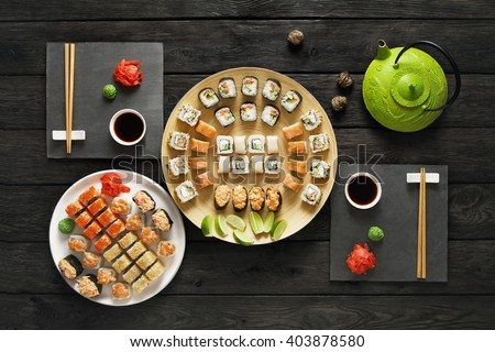 Japanese food restaurant, sushi maki gunkan roll plate or platter set. Set for two with chopsticks, ginger, soy, wasabi and teapot. Sushi at rustic wood background and black stone. Top view at black. - stock photo