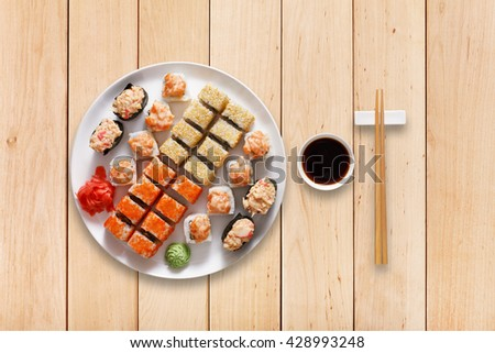 Japanese food restaurant, sushi maki gunkan roll plate or platter set. Set for two with chopsticks, ginger, soy, wasabi. Sushi at wooden planks background. Top view, flat lay. - stock photo