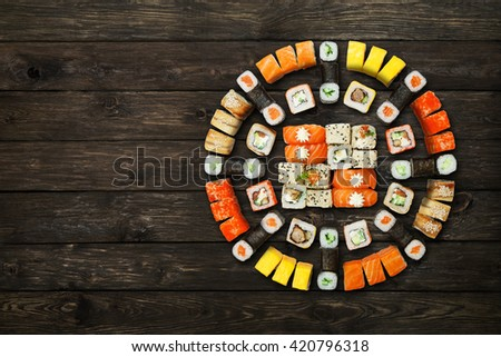 Japanese food restaurant, sushi maki gunkan roll plate or platter set. Set with colorful chopsticks, ginger, soy, wasabi. Sushi at rustic wood background and black stone. Top view with copyspace - stock photo