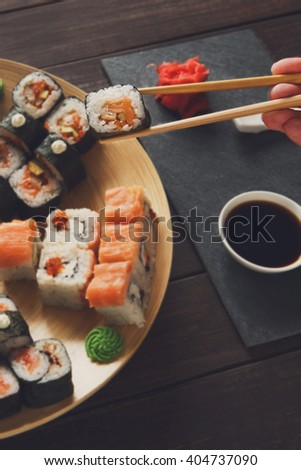 Japanese food restaurant, sushi maki roll plate, platter set. Hand take roll. Set for two with chopsticks, ginger, soy, wasabi. Sushi at rustic wood background and black stone. POV at black. Vertical. - stock photo