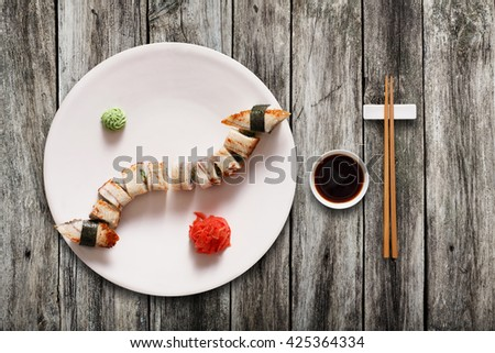 Japanese food restaurant, unagi sushi maki gunkan roll plate or platter set. Set for two with chopsticks, ginger, soy, wasabi. Sushi at rustic wood background. Top view, flat lay. - stock photo