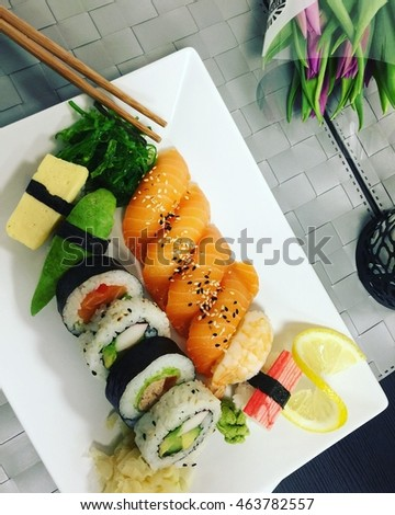 Japanese food. Sushi. Rolls. Food photography. Plate with meal on the grey background with flowers