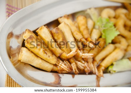 Japanese fried prawns in a steel tray, bamboo mat and chopsticks on white background