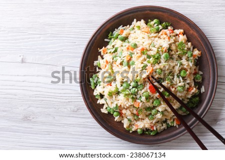 Japanese fried rice with green peas and eggs on the table. horizontal view from above - stock photo
