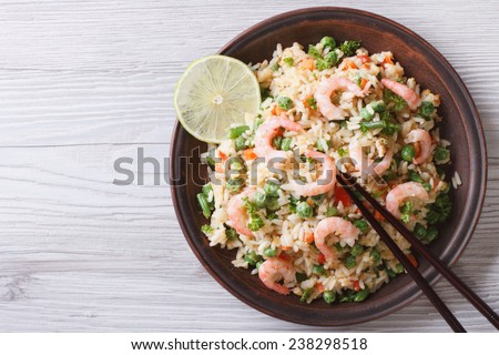 Japanese fried rice with seafood, eggs and vegetables on a plate close-up, horizontal view from above  - stock photo
