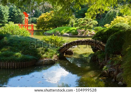 Japanese Garden and pond with a red Zen Tower. - stock photo