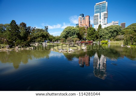 Japanese garden and the skyscrapers on a background of blue sky - stock photo