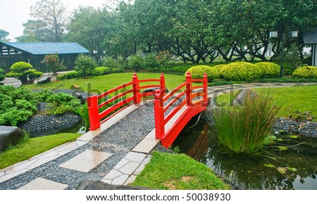 Japanese Garden With Red Bridge And Water.